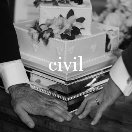 Two grooms hand in front of wedding cake